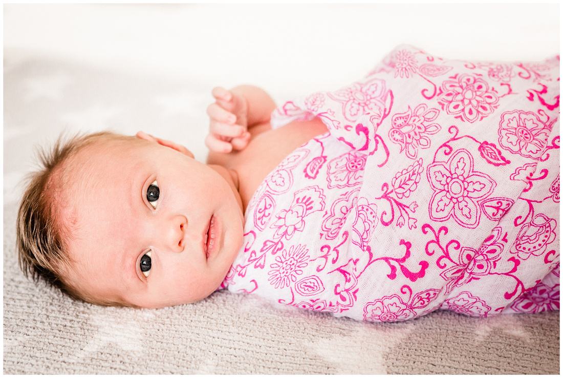 newborn baby girl wrapped in a pink and white blanket