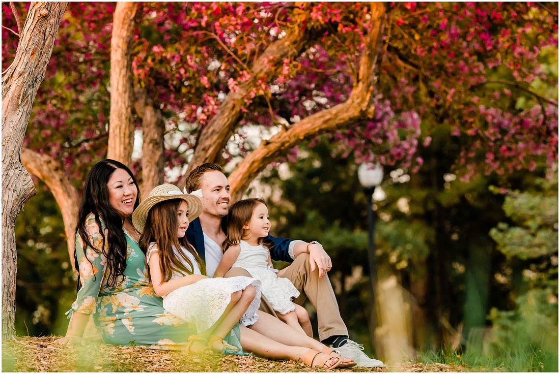 A family with dad, mom, and two girls photographed in front of flowering trees