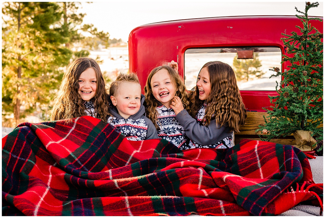 Children wearing pajamas in the back of a Model A truck for Christmas photos